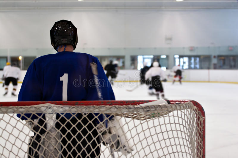 Hockey Goalie. A hockey goalie awaiting the return of the puck so he can resume his defensive role. Shallow depth of field royalty free stock photography