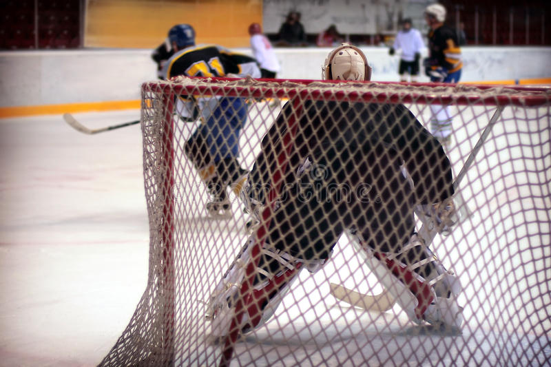 Hockey goalie. In generic black equipment protects gate royalty free stock photos