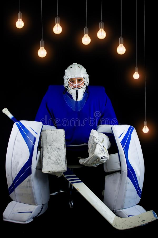 Hockey goalie in complete hockey outfit sitting on office chair. Above him are lamps with a light bulb on. royalty free stock photography