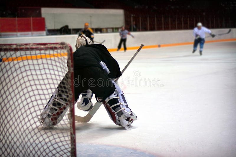 Hockey goalie. In generic black equipment protects gate stock photos