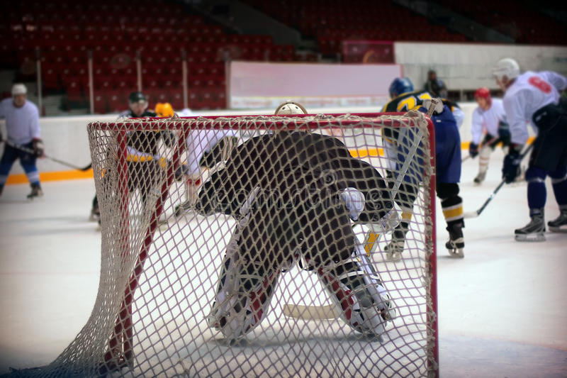 Hockey goalie. In generic black equipment protects gate royalty free stock photo