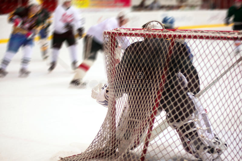 Hockey goalie. In generic black equipment protects gate stock image