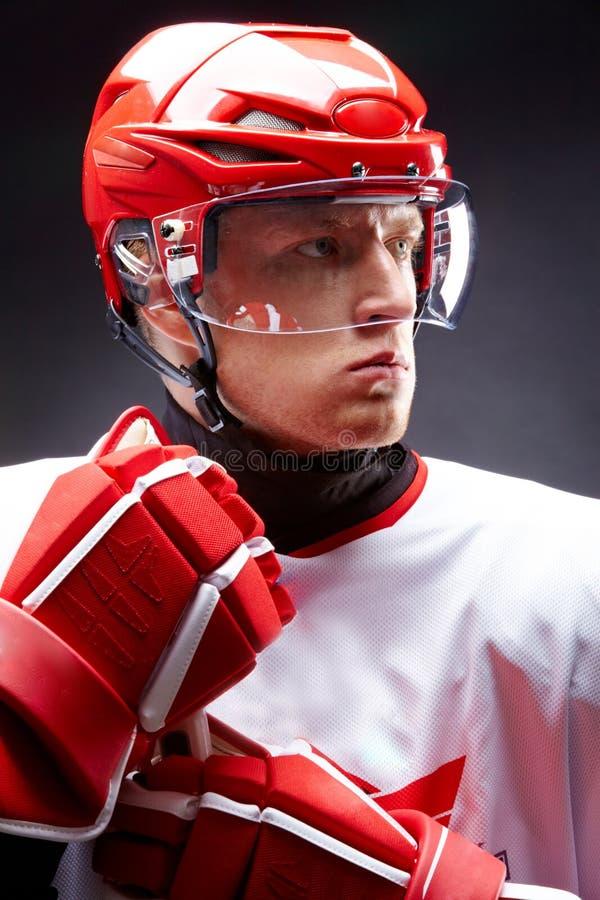Hockey man. Portrait of sportsman in hockey uniform over black background royalty free stock photo
