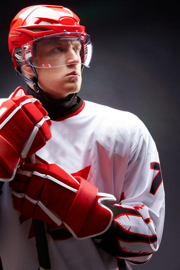 Hockey man. Portrait of sportsman in hockey uniform over black background stock image
