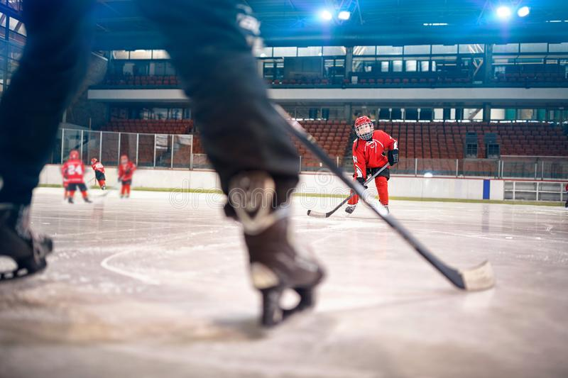 Hockey match at rink boy player in action. Kicking on goal royalty free stock images