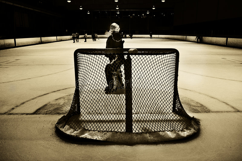 Hockey net and goalie. Goalie looking up at the scoreboard above the hockey net stock image
