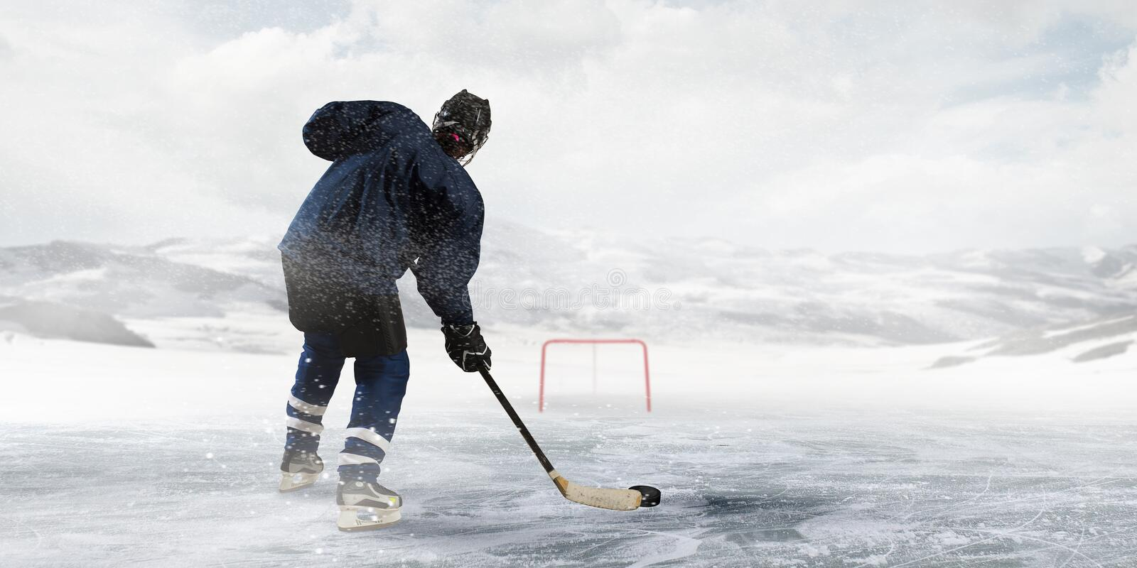 Hockey player on the ice. Hockey player aiming to gates outdoors at winter royalty free stock images