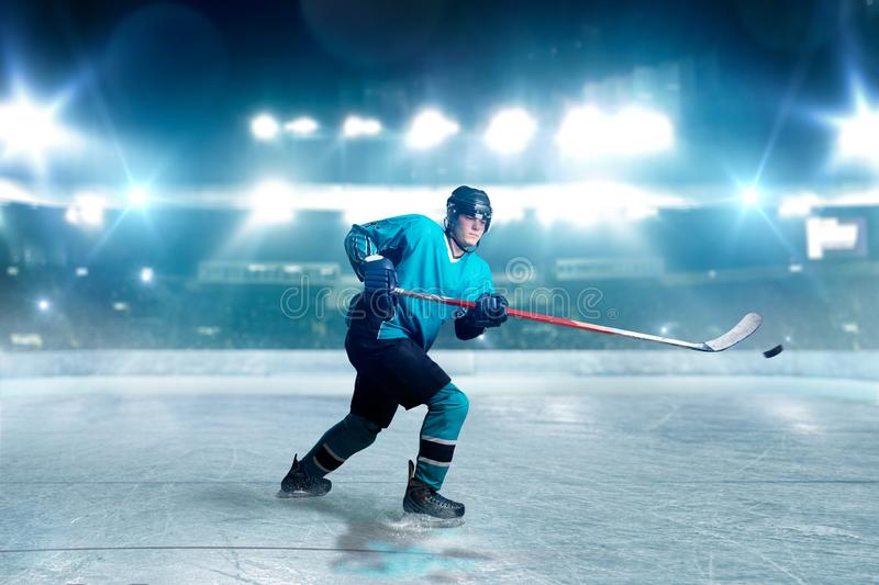 Hockey player with stick and puck makes a throw. Ice arena, spotlights on background. Male person in helmet, gloves and uniform playing game royalty free stock image