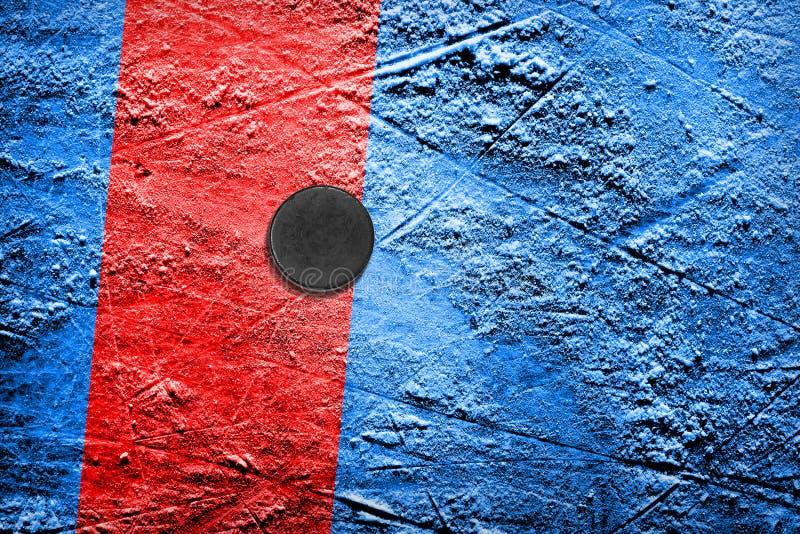 Hockey-Puck auf blauem Eis mit rotem Streifen stockbild