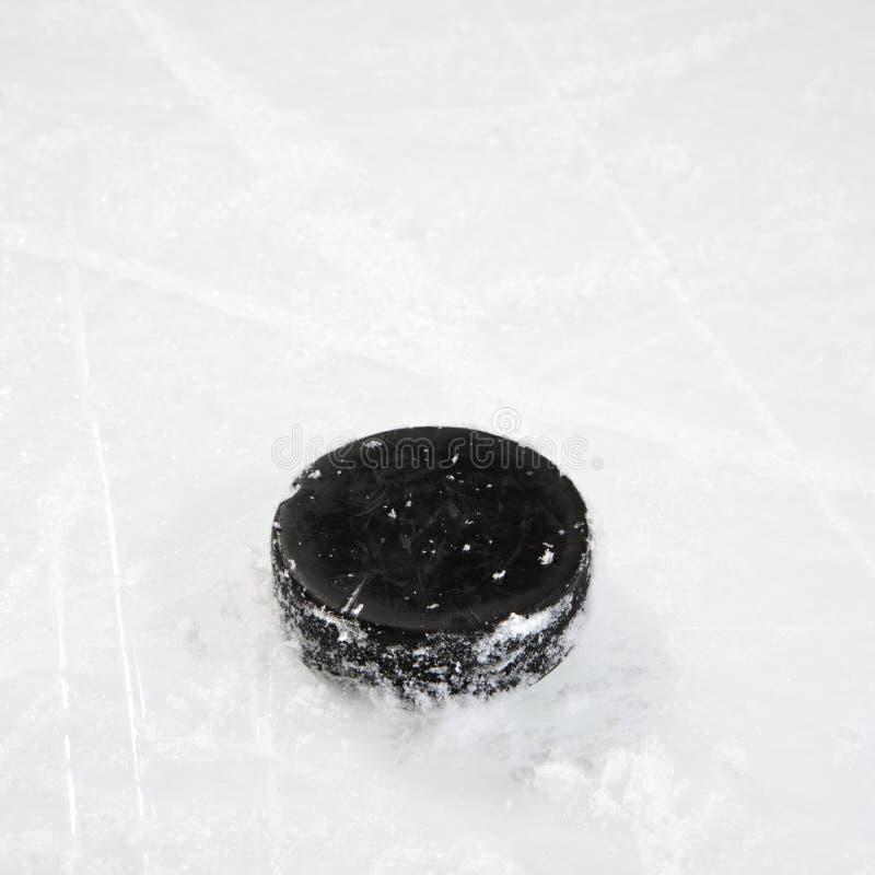 Hockey puck on ice. Black hockey puck on ice rink stock photography