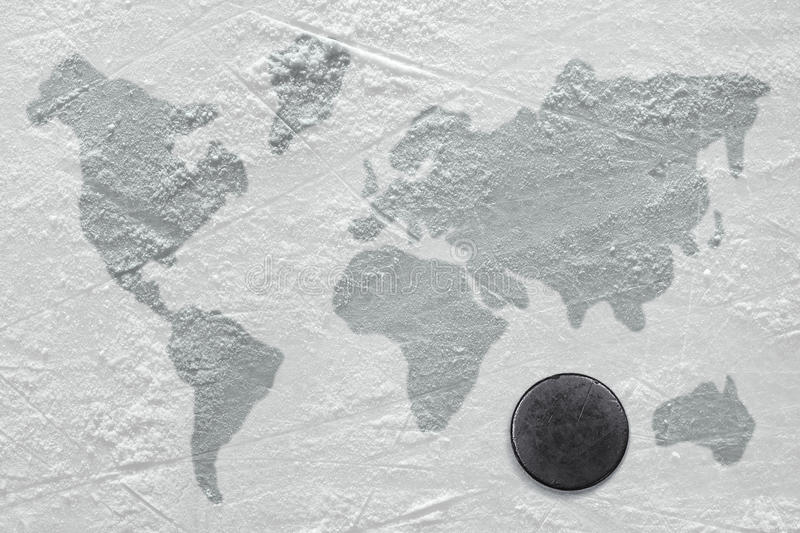 Hockey puck on ice. Hockey puck on the ice with the image of a world map royalty free stock image