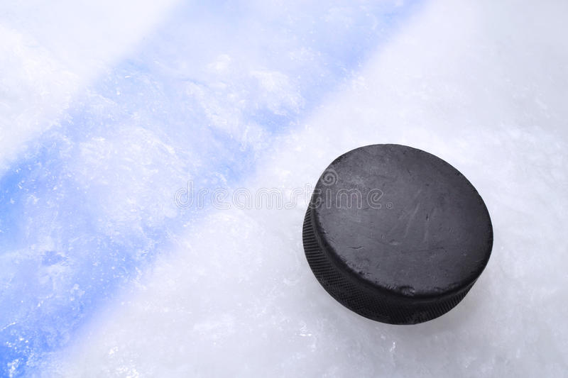 Hockey puck on ice. Vintage old hockey puck is on the ice near the blue line royalty free stock photo
