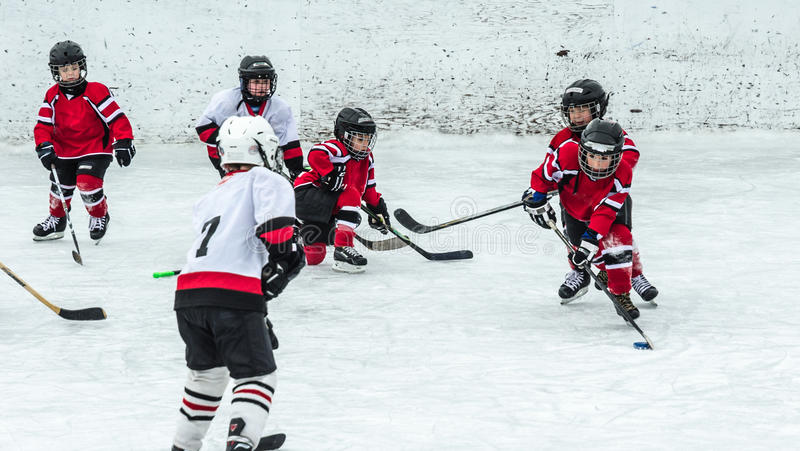 Hockey season, kids play national game at a winter carnival. Kids at a winter carnival enjoy the fun and action of playing Canada`s nationally celebrated game royalty free stock photography