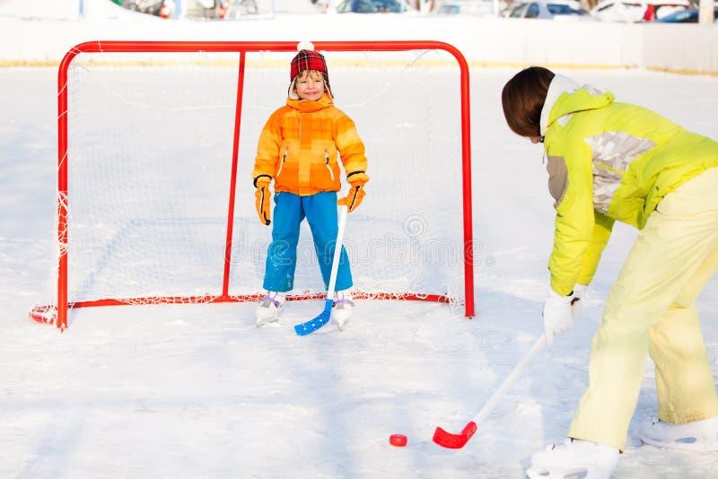 Hockey sobre hielo del juego de la madre con el hijo afuera fotografía de archivo libre de regalías
