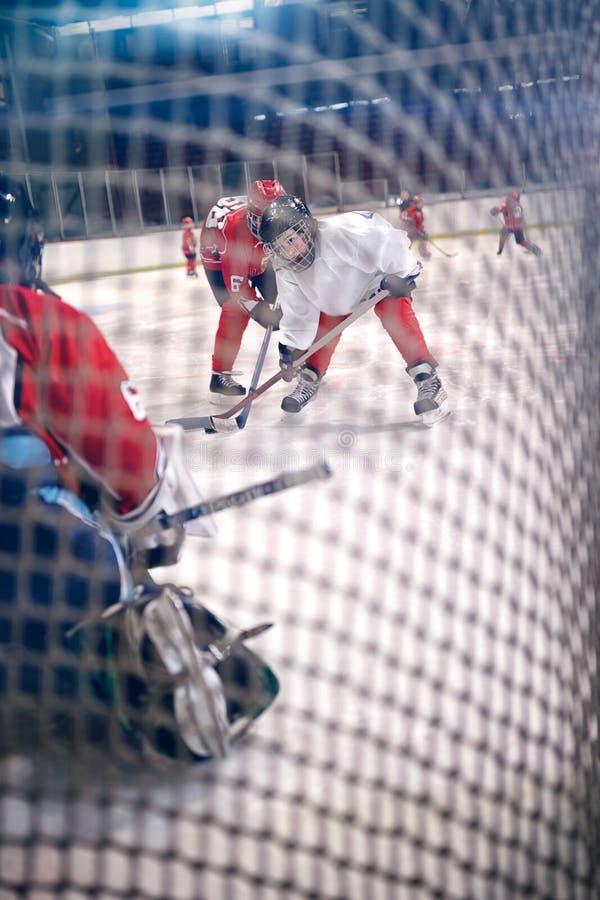 Hockeyspelare skjuter pucken och anfaller arkivbilder