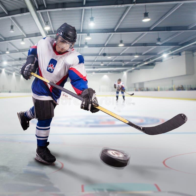 Hockeyspelaren skjuter pucken och anfaller målvakten royaltyfri bild