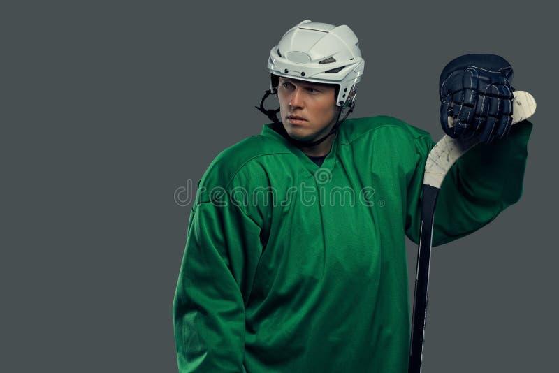Hockeyspeler die groen beschermend toestel en witte helm dragen die zich met de hockeystok bevinden geïsoleerd op grijs stock afbeelding