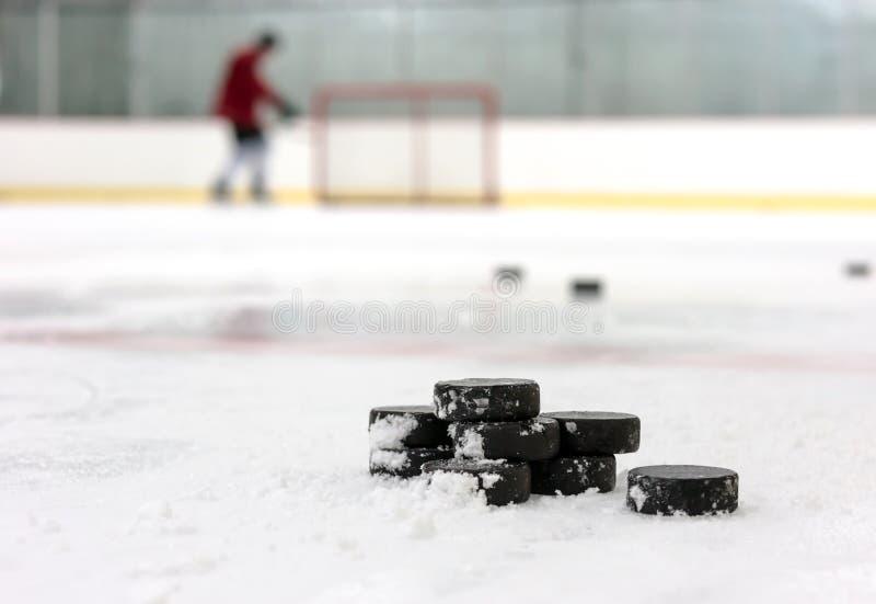 Hockeyspeler met stapel pucks royalty-vrije stock foto's