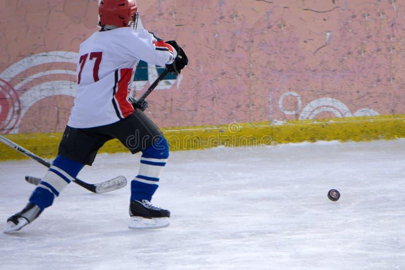 Hockeyspieler schießt den Kobold und die Angriffe lizenzfreies stockbild