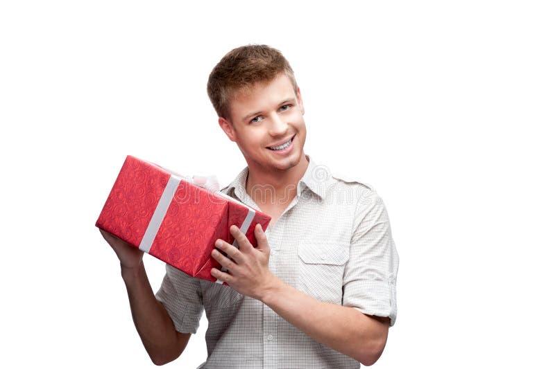 Hoding Geschenk des jungen zufälligen Mannes Weihnachts stockfotografie