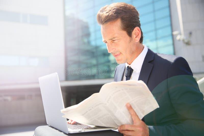 Hoding tidning och arbete för affärsman på bärbara datorn royaltyfria foton