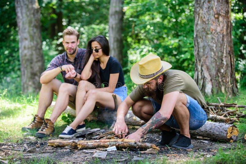 Hoe bouwstijlvuur in openlucht Het kamperen weekendvrije tijd Schik houttakjes of stokken Treft mensen brutale gebaarde hipster v stock foto