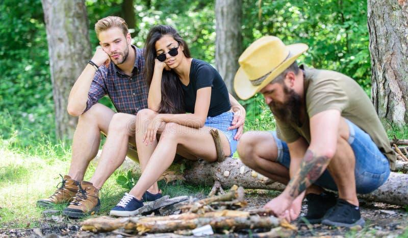 Hoe bouwstijlvuur in openlucht Het kamperen weekendvrije tijd Schik houttakjes of stokken Treft mensen brutale gebaarde hipster v stock foto's