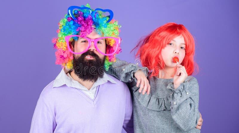 Hoe gek uw vader is Dragen het de mensen gebaarde vader en meisje kleurrijke pruik terwijl lollysuikergoed eet de dings houdende  stock fotografie