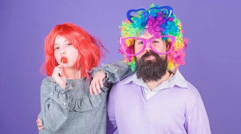 Hoe gek uw vader is Dragen het de mensen gebaarde vader en meisje kleurrijke pruik terwijl lollysuikergoed eet de dings houdende  royalty-vrije stock foto