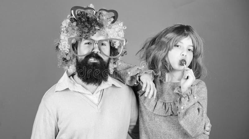 Hoe gek uw vader is Dragen het de mensen gebaarde vader en meisje kleurrijke pruik terwijl lollysuikergoed eet de dings houdende  stock foto