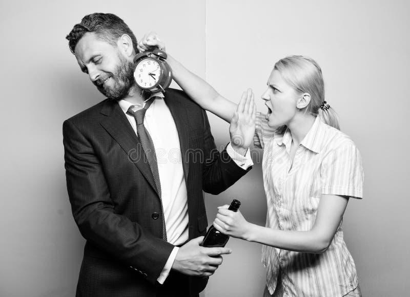 Hoe laat het is Zakenman met alcoholfles en vrouw met wekker Mens die aan alcoholisme lijden Boze vrouw stock fotografie
