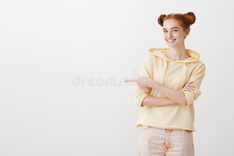Hoe over wij in die richting gaan Binnenschot van positieve roodharige vrouwelijke student die met twee broodjeskapsel glimlachen royalty-vrije stock foto's