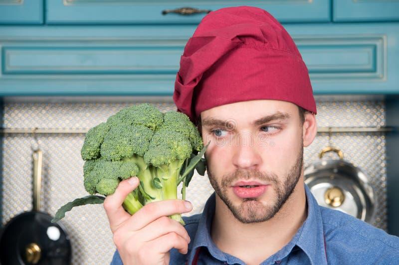 Hoe te om broccoli te koken De organische broccoli van de mensengreep Mens klaar om natuurvoeding te koken Vitaminevoeding De vit stock afbeelding