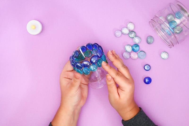 Hoe te om uw eigen kandelaar van onnodige glas of plastiek en glaskiezelstenen te maken Stap voor stap Kerstmis binnenlands decor stock foto
