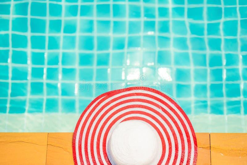 Hoed aan de kant van zwembad, het concept van de de zomerreis stock fotografie