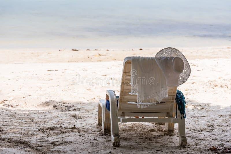 Hoed, een handdoek die op een stoel op het strand door het overzees hangen thailand royalty-vrije stock afbeeldingen