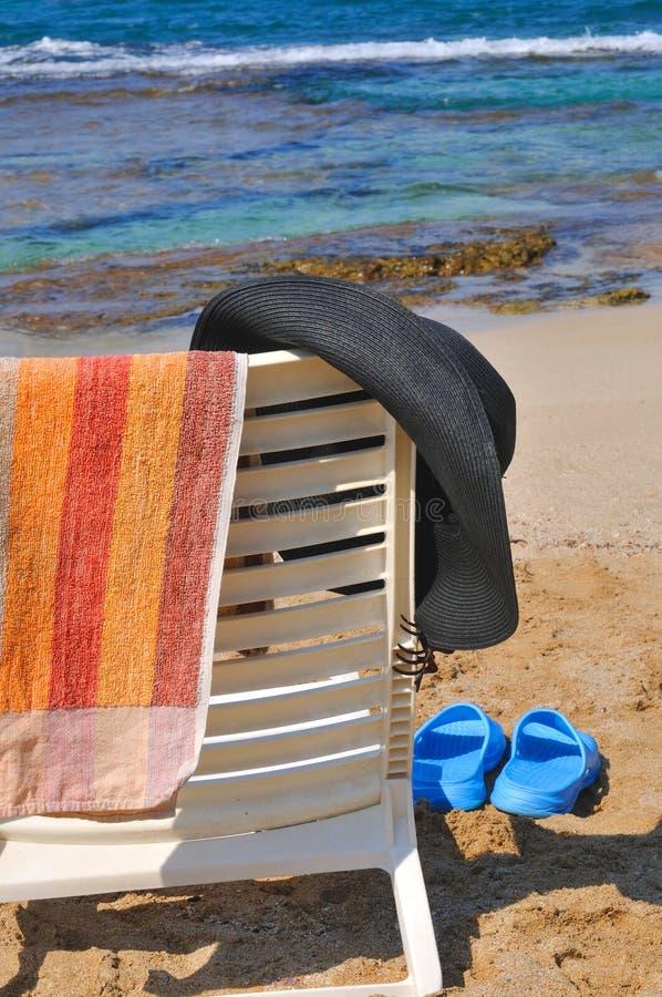 Hoed en handdoek op een stoel door het overzees stock afbeeldingen