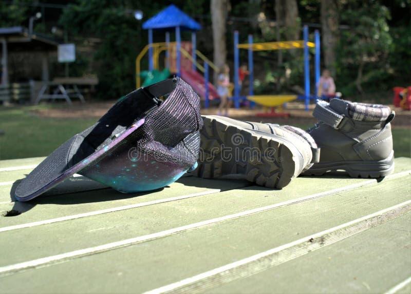 Hoed en laarzen met kinderen die op ritten in park spelen royalty-vrije stock fotografie