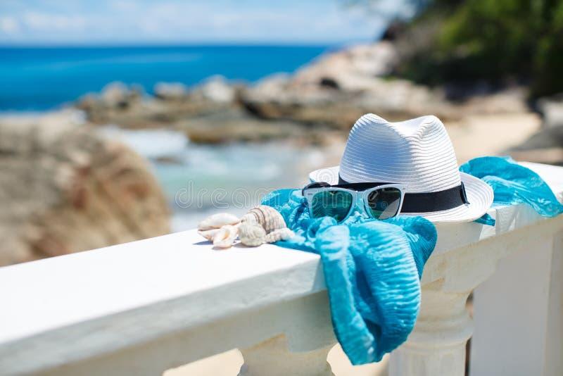 Hoed en zonnebril op achtergrond van oceaanstrand royalty-vrije stock afbeelding