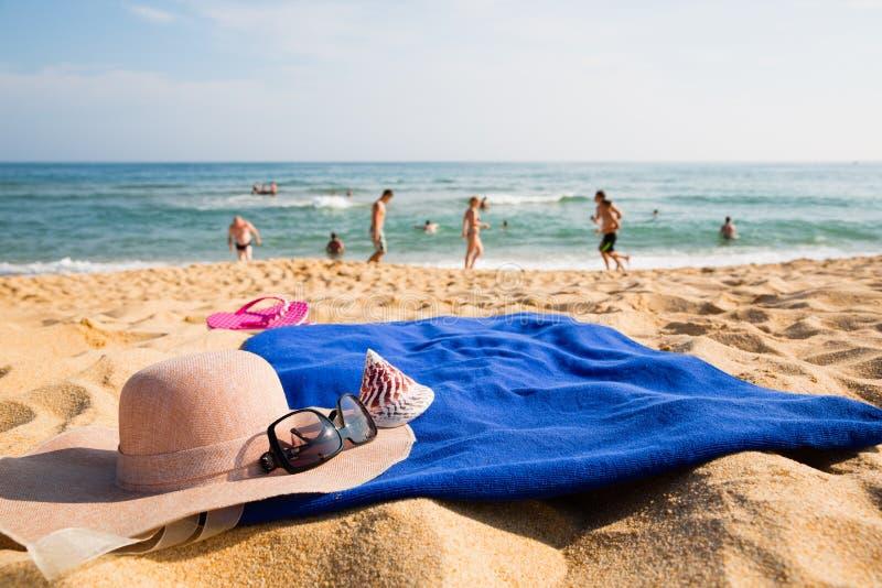 Hoed, handdoek, zonnebril en pantoffels op een tropisch strand stock fotografie