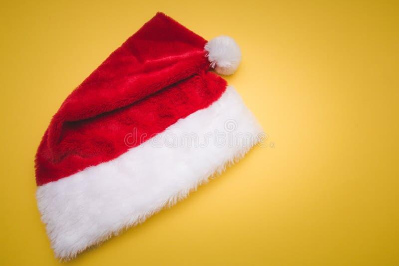 Hoed van Kerstmis de rode Santa Claus met witte gele pompom De achtergrond van de decoratie royalty-vrije stock fotografie