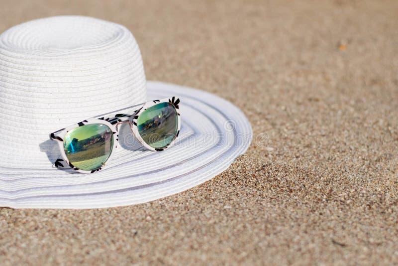 Hoeden en glazen die op het strand worden geplaatst royalty-vrije stock fotografie