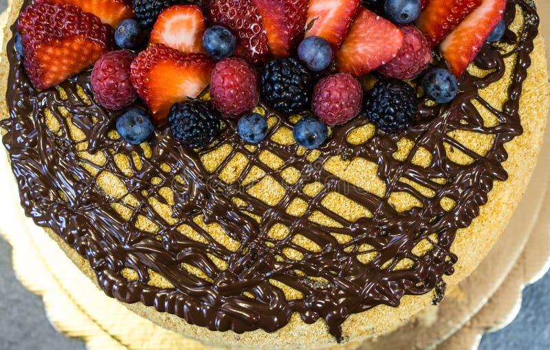 Hoedenpastei, chocolade op hoogste, sappige aardbeien, frambozen, en bessen, mening van hierboven stock fotografie