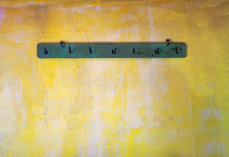 Hoedenplank op oude gele muur stock foto