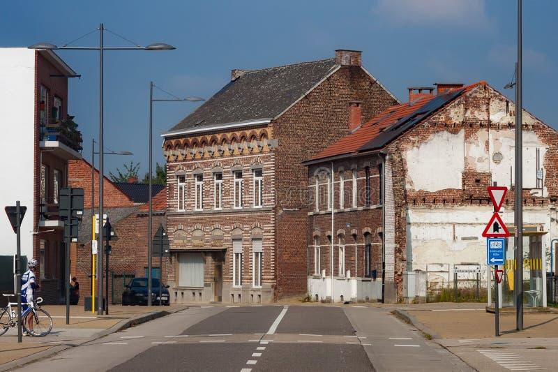HOEGAARDEN BELGIEN - SEPTEMBER 04, 2014: Gamla byggnader för röd tegelsten i mitten av Hoegaardenen på den Stationsstraat gatan royaltyfria foton