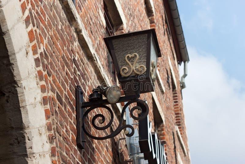 HOEGAARDEN, BELGIO - 4 SETTEMBRE 2014: Lampada di via d'annata del ferro sulla parete di vecchia costruzione di mattone rosso fotografia stock