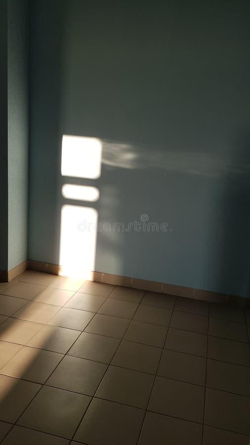 Hoek binnen lege ruimte en betegelde vloer met heldere glanzende onscherpe zonnestralen stock foto