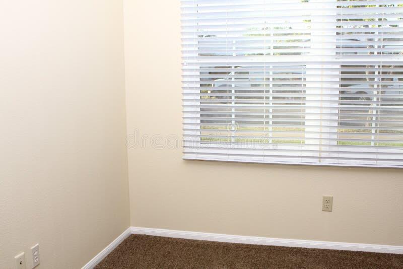 Hoek van binnenlandse muren en nieuw zonneblinden en tapijt stock foto