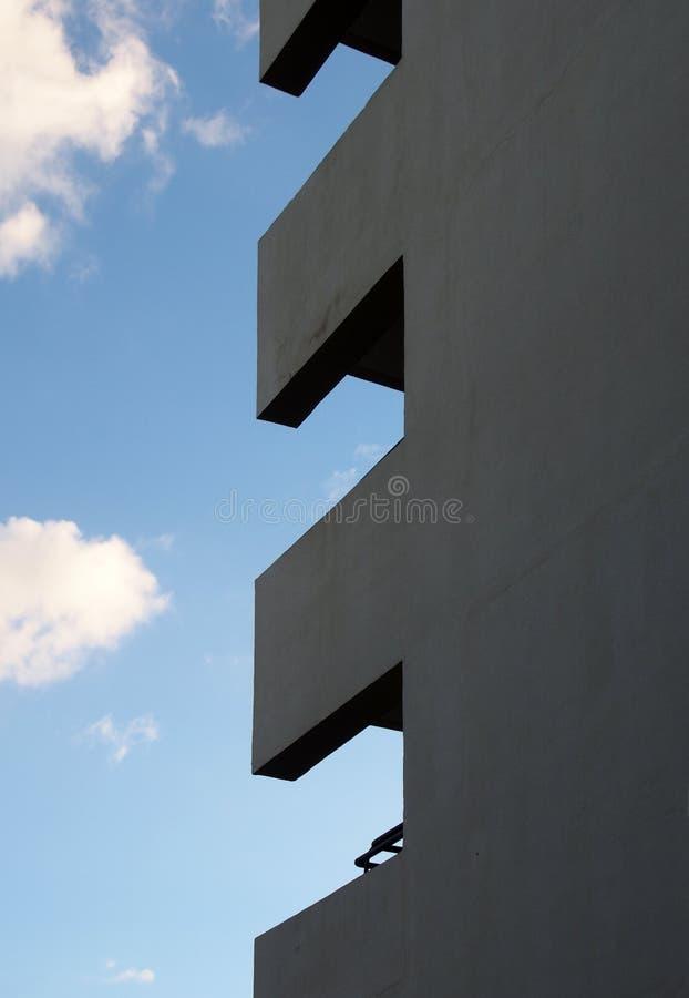 Hoek van een lang flatgebouw met balkons die geometrische vormen vormen tegen een blauwe bewolkte hemel stock afbeeldingen