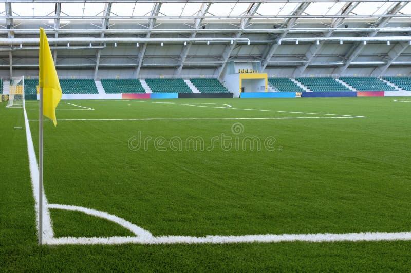 Hoek van een voetbalgebied in een binnenstadion Gele vlag, wit die op groen gras merken Toeschouwerstribunes op de achtergrond ex stock foto's